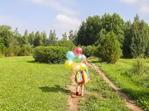 Adorable little girl on green grass with colorful bright balloons stock photos