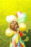 Adorable little girl on green grass with colorful bright balloons stock images