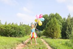 Adorable little girl on green grass with colorful bright balloons royalty free stock photo