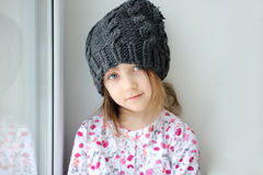 Adorable little girl in grey knit. Adorable little kid girl with blue eyes in dark grey knit hat near the window looks into the camera Stock Image