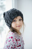 Adorable little girl in grey knit hat. Adorable little kid girl with blue eyes in dark grey knit hat near the window looks into the camera Stock Photography