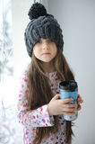 Adorable little girl in grey knit hat with cup Stock Images