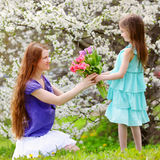 Adorable little girl handing tulips to her mother in blooming cherry garden Stock Photography