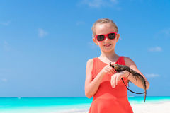 Adorable little girl happily holds a wild tropical lizard on white tropical beach Stock Photo
