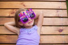 Adorable little girl in Happy Birthday glasses. Have fun outdoor. This image has attached release Stock Image