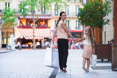 Adorable little girl and happy mother walking with shopping bags in Paris outdoors Stock Photo