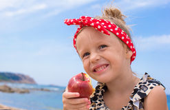 Adorable little girl have fun eating an apple Stock Images