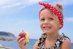 Adorable little girl have fun eating an apple Royalty Free Stock Photos