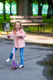 Adorable little girl have fun on the scooter Stock Images