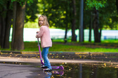 Adorable little girl have fun on the scooter Royalty Free Stock Photo