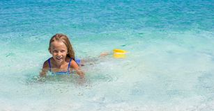 Adorable little girl have fun in shallow water at Royalty Free Stock Image