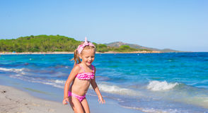 Adorable little girl have fun in shallow water at. Cute toddler girl standing in shallow water at exotic beach Royalty Free Stock Photo