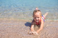 Adorable little girl have fun at shallow water on Stock Photography