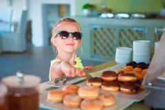 Adorable little girl having breakfast at cafe early in the morning Royalty Free Stock Image