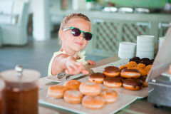 Adorable little girl having breakfast at cafe early in the morning Stock Photography