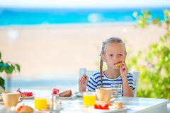 Adorable little girl having breakfast at cafe with sea view early in the morning Stock Photos