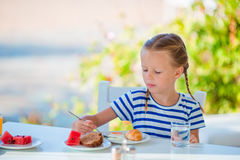 Adorable little girl having breakfast at cafe with sea view early in the morning Royalty Free Stock Photos