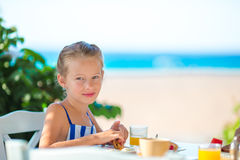 Adorable little girl having breakfast at cafe with sea view Royalty Free Stock Images