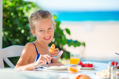 Adorable little girl having breakfast at cafe with sea view Stock Images