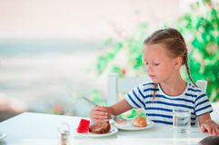 Adorable little girl having breakfast at cafe with sea view Royalty Free Stock Photos