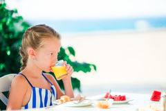 Adorable little girl having breakfast at cafe with sea view Royalty Free Stock Photography