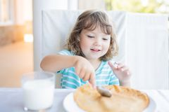 Adorable little girl having breakfast, eating pancakes and drinking milk royalty free stock photo