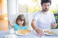 Adorable little girl having breakfast with her father, eating pancakes and drinking milk stock photography