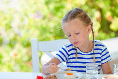 Adorable little girl having breakfast at outdoor cafe early in the morning Royalty Free Stock Photos