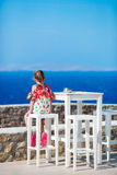 Adorable little girl having breakfast at outdoor cafe with sea view. Time for lunch. Royalty Free Stock Photo