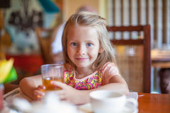 Adorable little girl having breakfast at resort Royalty Free Stock Photos