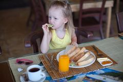 Adorable little girl having breakfast at resort Stock Images