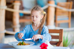 Adorable little girl having dinner at outdoor cafe Royalty Free Stock Photo