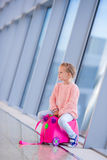 Adorable little girl having fun in airport sitting on her luggage. Adorable little girl at airport sitting on suitcase Stock Images