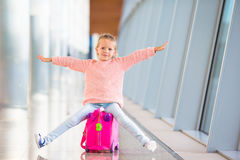 Adorable little girl having fun in airport sitting. Adorable little girl at airport sitting on suitcase Stock Photos
