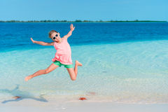 Adorable little girl having fun on the beach full of starfish on the sand Royalty Free Stock Image