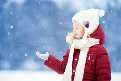 Adorable little girl having fun in beautiful winter park. Cute child playing in a snow. stock image