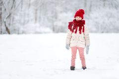 Adorable little girl having fun in beautiful winter park. Cute child playing in a snow. Stock Photos