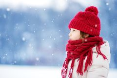 Adorable little girl having fun in beautiful winter park. Cute child playing in a snow. stock photography