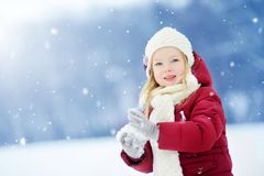 Adorable little girl having fun in beautiful winter park. Cute child playing in a snow. Royalty Free Stock Image