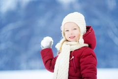 Adorable little girl having fun in beautiful winter park. Cute child playing in a snow. royalty free stock photos
