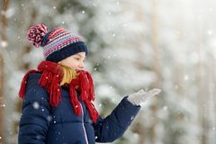 Adorable little girl having fun in beautiful winter park. Cute child playing in a snow. stock images