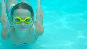 Adorable little girl having fun in outdoor swimming pool. Cute little girl in the water park swimming underwater and smiling stock video footage