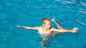 Adorable little girl in outdoor swimming pool stock video