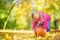 Adorable little girl having fun on a pumpkin patch on beautiful autumn day. Outdoors. Happy child playing in autumn park. Kid gathering yellow fall foliage Royalty Free Stock Image