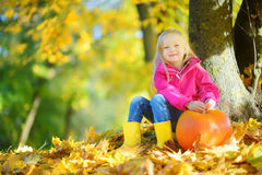 Adorable little girl having fun on a pumpkin patch on beautiful autumn day Royalty Free Stock Photography