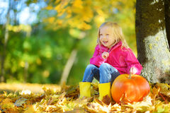 Adorable little girl having fun on a pumpkin patch on beautiful autumn day Royalty Free Stock Photos