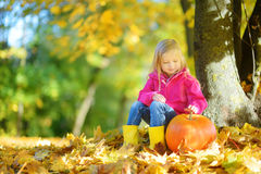Adorable little girl having fun on a pumpkin patch on beautiful autumn day Royalty Free Stock Images