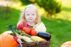 Adorable little girl having fun on a pumpkin patch Stock Photo