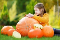 Adorable little girl having fun on a pumpkin patch Stock Photos
