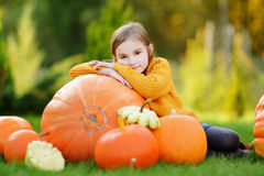 Adorable little girl having fun on a pumpkin patch Stock Images